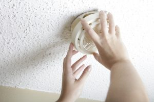 female-hands-opening-smoke-detector-to-change-battery