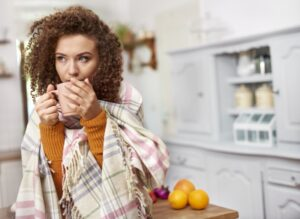 woman-wrapped-in-blanket-sipping-from-mug