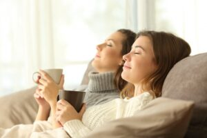 two-women-leaning-back-on-couch-with-mugs-looking-comfortable